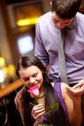 Image of pretty woman smelling rose and touching man's hand Stock Photos