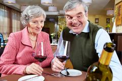 image of couple looking at good wine while sitting at a restaurant - stock photo
