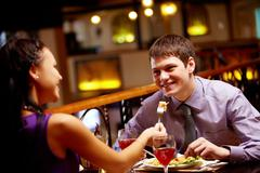 Woman spoon-feeds her boyfriend in the restaurant Stock Photos