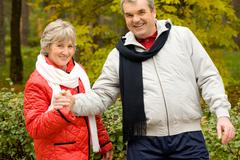Photo of two aged people looking at camera during walk in autumn forest Stock Photos