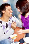 happy girl and handsome man looking at each other while eating ice-cream in cafe - stock photo
