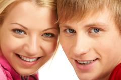 Happy faces of young girl and guy looking at camera and smiling Stock Photos
