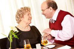 Portrait of mature man holding woman's hand with love and looking at her Stock Photos