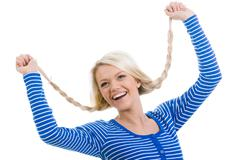 Stock Photo of above view of happy girl with raised arms holding her pigtails over white backgr