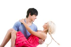 Image of beautiful blonde looking at handsome man while on his arms Stock Photos