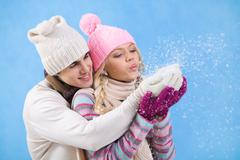 portrait of happy young couple in warm clothes blowing snow off their palms - stock photo