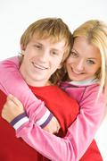 portrait of happy guy being hugged by his pretty girlfriend - stock photo
