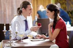 Image of elegant man making proposal to beautiful woman in restaurant during rom Stock Photos