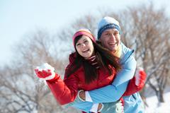 Photo of happy guy embracing joyful girl and both laughing during winter vacatio Stock Photos