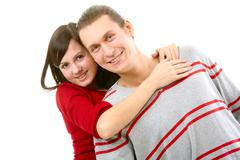portrait of attractive young girl embracing her boyfriend over white background - stock photo