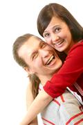 portrait of attractive young girl embracing her boyfriend and both laughing - stock photo