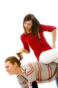 portrait of attractive young girl pulling her boyfriend hair while sitting on hi - stock photo
