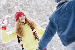 image of attractive young woman flinging the snowball into her boyfriend - stock photo