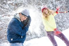 Image of young woman flinging the snowball into her boyfriend Stock Photos