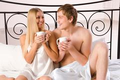 Photo of happy husband and wife drinking tea while sitting on bed in the morning Stock Photos