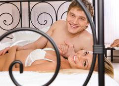 Photo of happy husband and wife lying on bed and looking at each other Stock Photos