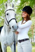 Image of happy female grooming purebred horse outdoors Stock Photos