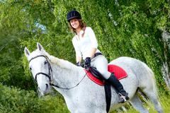 image of happy female jockey on purebred horse outdoors - stock photo