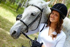 image of happy female in riding cap embracing purebred horse and looking at came - stock photo