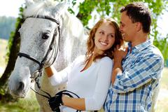 image of happy woman with purebred horse and her sweetheart near by - stock photo