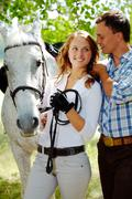image of happy woman between purebred horse and her sweetheart outside - stock photo