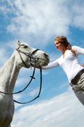 image of happy female grooming purebred horse against cloudy sky - stock photo
