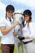 Image of happy couple with purebred horse looking at camera Stock Photos