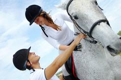 image of handsome man helping woman to sit on purebred horse - stock photo