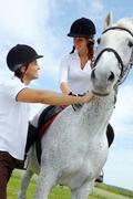 image of handsome man giving instructions to woman sitting on purebred horse - stock photo