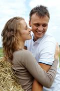 happy man laughing while being embraced by beautiful woman outdoor - stock photo