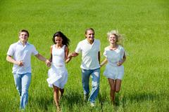 Stock Photo of portrait of happy girls and guys running down green grass on summer day
