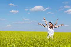 Image of joyful girl and her boyfriend standing in yellow meadow with raised arm Stock Photos