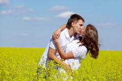 Image of amorous couple kissing in yellow meadow at summer Stock Photos