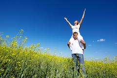 Portrait of young man holding his happy girlfriend on shoulders Stock Photos