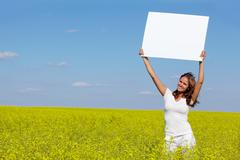 Portrait of charming girl with blank paper standing in meadow Stock Photos