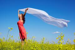 Image of happy woman holding a white fabric in the yellow meadow Stock Photos