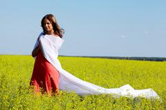 image of happy woman folded in white fabric in the yellow meadow - stock photo