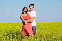 Image of happy couple in yellow meadow at summer looking at camera Stock Photos