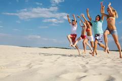 photo of happy friends running down sandy beach with raised arms - stock photo