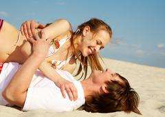 Photo of smiling girl and her boyfriend embracing while sunbathing on the beach Stock Photos