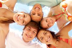 Below view of joyful teens embracing and looking at camera with smiles Stock Photos