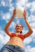 photo of happy girl in bikini holding ball on background of cloudy sky - stock photo