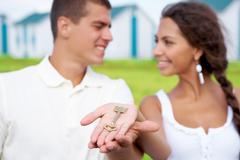 Attractive couple smiling at each other with stretched palms holding key outdoor Stock Photos