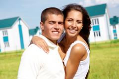 portrait of happy couple smiling at camera while embracing outdoors - stock photo