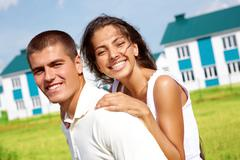 portrait of happy couple smiling at camera outdoors on background of new houses - stock photo