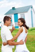 Glad couple smiling at each other while guy showing thumb up with nice house out Stock Photos
