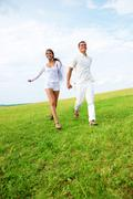 photo of young man and woman running down bright green grass on summer - stock photo