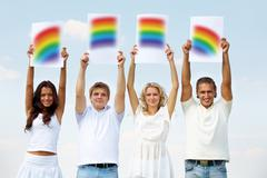 Portrait of happy girls and guys holding papers with rainbow parts outside Stock Photos