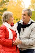 Photo of two aged people looking at one another in autumn forest Stock Photos