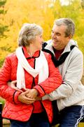 photo of two aged people looking at one another in autumn forest - stock photo